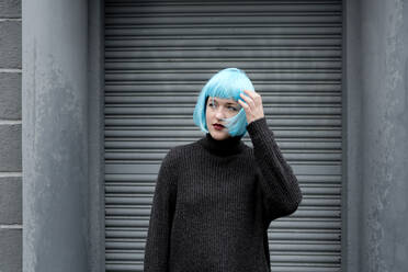 Young woman wearing blue wig, hand in hair - FLLF00386