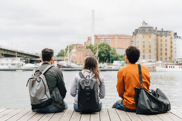 Rear view of friends with backpacks sitting on pier by river in city against sky - MASF16429