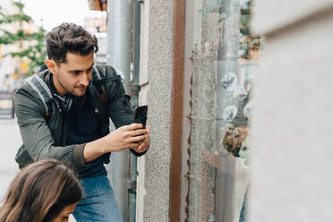 Young man photographing store window with mobile phone while standing with friend in city - MASF16432