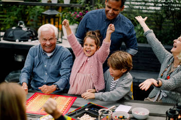 Cheerful multi-generation family playing board game on table while sitting in patio - MASF16462