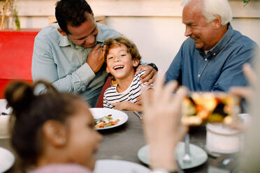 Senior woman photographing happy family at dining table during lunch - MASF16468