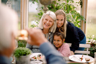 Senior man photographing smiling family with mobile phone during lunch - MASF16471
