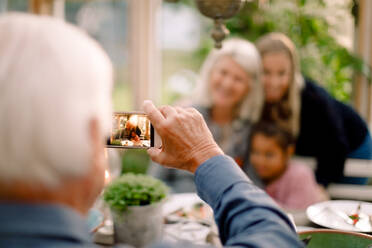 Senior man photographing happy family with mobile phone during lunch - MASF16474