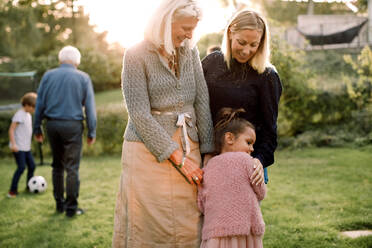 Girl embracing with mother and grandmother while standing in backyard - MASF16477