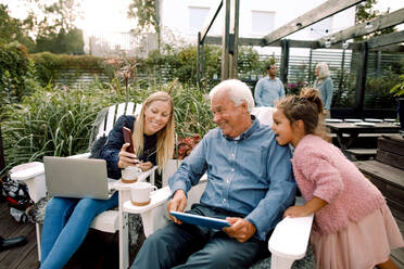 Smiling family using digital technology while sitting in backyard during weekend - MASF16489