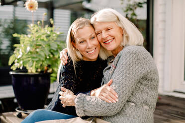 Smiling mother and daughter with arm around sitting in backyard - MASF16498