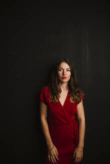Portrait of young woman wearing red dress - LJF01236