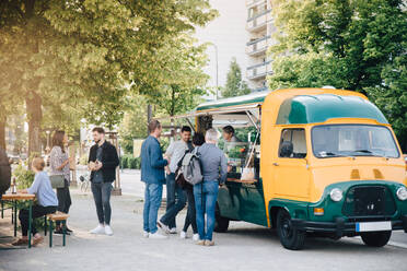 Male and female customers standing by food truck - MASF16557