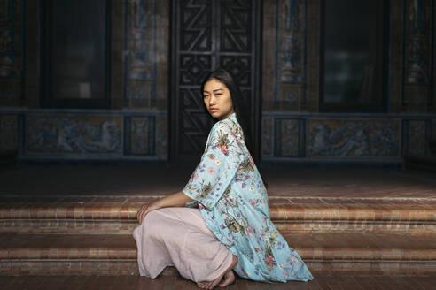 Portait of beautiful young woman sitting on steps wearing a kimono - TCEF00164
