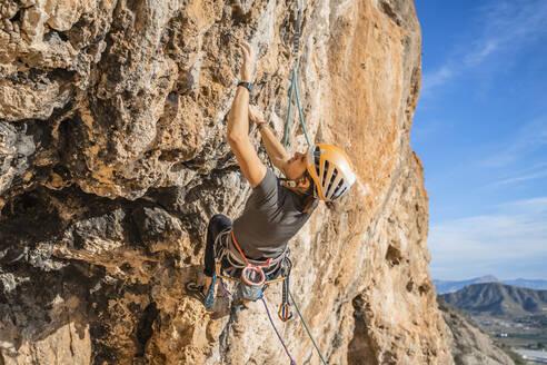 Woman climbing at rock face - DLTSF00454