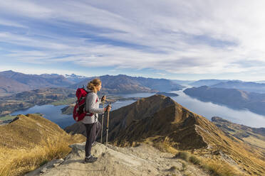 Woman standing on viewpoint at Roys Peak, looking to Mount Aspiring, Lake Wanaka, South Island, New Zealand - FOF11835