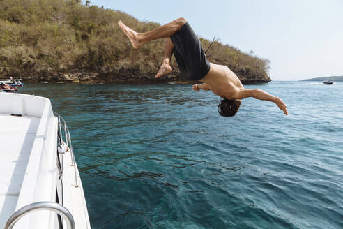 Young man jumping from a boat, Lembongan island, Bali, Indonesia - KNTF04249