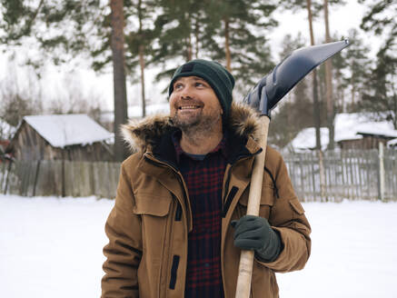 Portrait of smiling man with snow shovel looking up - KNTF04262