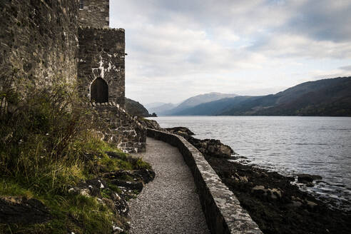 Castle in wall overlooking a loch with mountains in the distance. - MINF13345