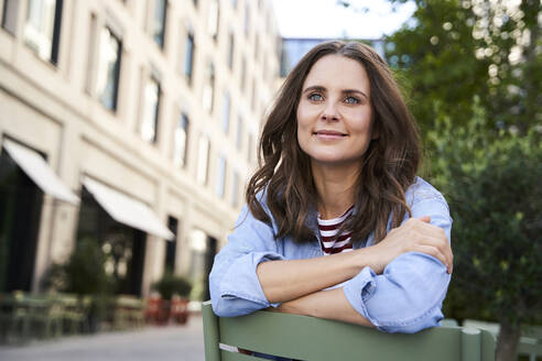 Portrait of smiling brunette woman sitting on a chair in the city - PNEF02236