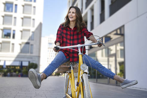 Happy brunette woman riding bicycle in the city - PNEF02254