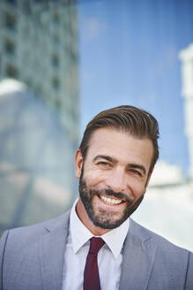 Portrait of happy businessman in the city - PNEF02281