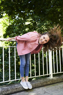 Portrait of happy brunette woman holding railing outdoors - PNEF02320
