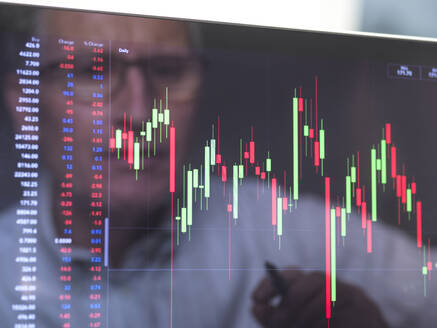 Reflection of a stock trader viewing the performance of a company share price on screen - ABRF00688