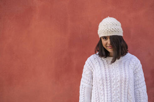 Portrait of smiling teenage girl in fornt of red wall wearing white knitwear - DLTSF00479