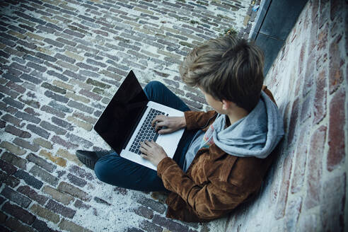 Teenager using laptop and sitting on a stone floor in the city - ANHF00181