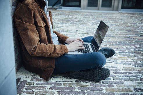 Teenager using laptop and sitting on a stone floor in the city - ANHF00187