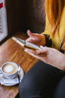 Crop view of young woman using smartphone in a coffee shop - LJF01269