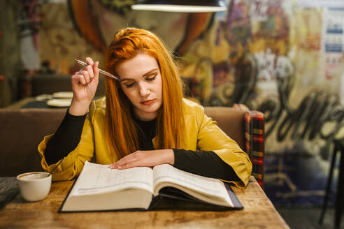 Portrait of redheaded young woman at table in a pub writing in a book - LJF01281