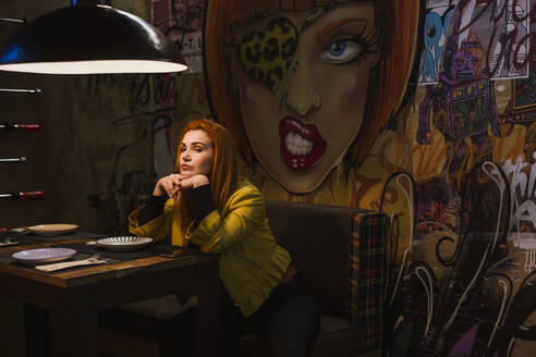Portrait of redheaded young woman waiting in a pub in front of graffiti wall - LJF01284