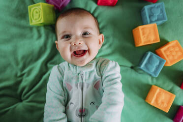 Portrait of happy baby girl lying on green mat among with rubber toys - GEMF03424