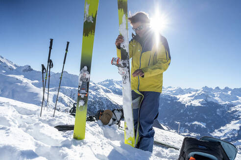 Man in backlight preparing ski for a ski tour, Grisons, Switzerland - HBIF00026