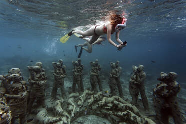 Women swimming near underwater sculptures made by Jason deCaires Taylor, Gili Meno island, Bali, Indonesia - KNTF04342