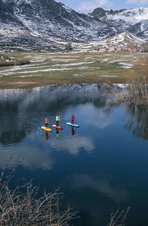 Aerial view of three people stand up paddle surfing, Leon, Spain - DGOF00324