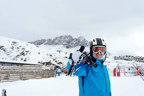 Portait of smiling man with skis in ski area - CJMF00248