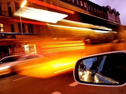 Germany, Berlin, Side mirror of car driving through city at dusk - BIGF00070