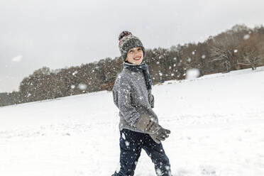 Portait of happy boy in winter landscape with snowfall - EYAF00935
