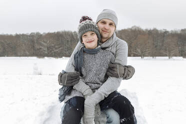 Portrait of happy father with this son in winter landscape - EYAF00938