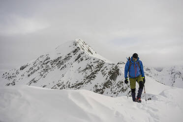 Man on an excursion on the crest of a snowy mountain, Lombardy, Valtellina, Italy - MCVF00222