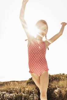 Portrait of happy girl in bathing suit dancing in backlight - SDAHF00115