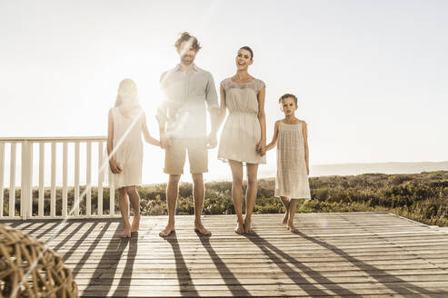 Family standing on terrace at the coast at sunset - SDAHF00142