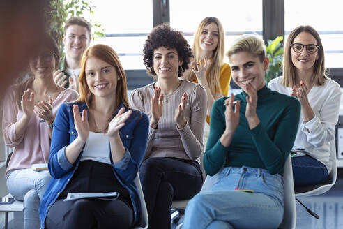 Businesswomen clapping hands during a training - JSRF00895