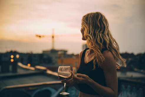 Thoughtful young woman having wine while looking away on terrace during rooftop party at sunset - MASF16648
