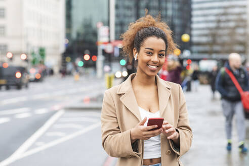 Smiling young woman with cell phone and earbuds in the city, London, UK - WPEF02554