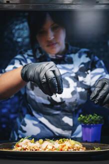Chef preparing a dish in restaurant kitchen - DGOF00369