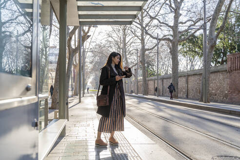 Young woman waiting at the tram stop - AFVF05292
