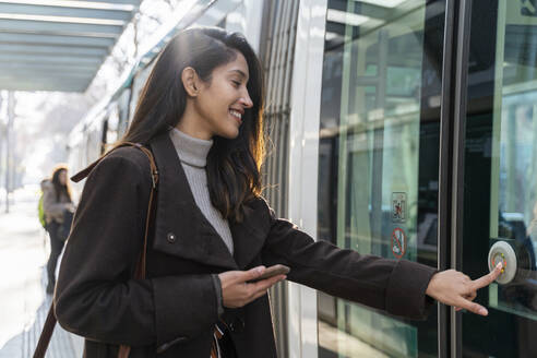 Smiling young woman pushing the button at a tram - AFVF05298