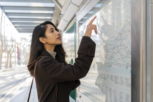 Young woman looking at map at the tram stop - AFVF05304