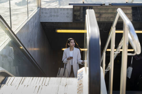 Young woman with smartphone leaving subway station - AFVF05382
