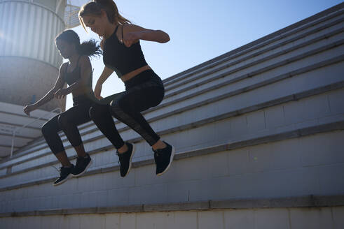 Sportswomen jumping from a stair - PACF00181