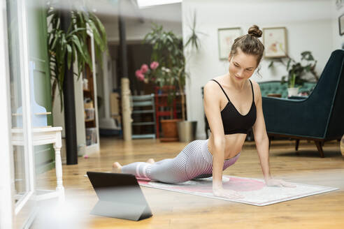 Young woman practicing yoga at home, using yoga app on digital tablet - PESF01778
